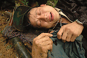 "Tong Fang, lays on the shallow grave of his wife mourning her loss, near Vang Vieng, Laos, July 1, 2006.  When we reached the site of the massacre Tong Fang fell onto the grave wrapping himself in her clothing riddled with bullet holes.  Tong was totally inconsolable.  He was an armed escort to the women and children hunting for food on April 6th, and was wounded, but his young wife was cut down by bullets and died in his arms.  His message to the Lao Government is, ""Our people are innocent civilians.  We had not commited any crimes.  Why did you kill our unarmed women and children?""..**EXCLUSIVE, no tabloids without permission**.The Hmong people pictured have hidden in remote mountains of Laos for more than 30 years, afraid to come out.  At least 12,000 are said to exist, with little food, scavenging in the jungle. Most have not seen the modern world.  Since 1975, under the communists, thousands of reports evidence the Hmong have suffered frequent persecution, torture, mass executions, imprisonment, and possible chemical weapons attacks.  Reports of these atrocities continue to this day.  The Lao Government generally denies the jungle people exist or that any of this is happening.  The Hmong group leader, Blia Shoua Her, says they are not part of the Hmong resistance and want peace.  He claims they are just civilians defending their families, hoping to surrender to the UN.  The Lao Spokesman for the Ministry of Foreign Affairs says this is a fabrication, an investigation has been completed, and there was no attack.  The Hmong group says no officials have interviewed witnesses or visited the crime scene, a point the Lao Spokesman did not deny.  .."