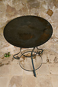 metal round garden table placed against a weathered brown wall
