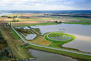 Nederland, Noord-Brabant, Werkendam, 23-10-2013; Ruimte voor de Rivier project Ontpoldering Noordwaard, rivier de Nieuwe Merwede links aam de horizon. Landschapskunstwerk De Wassende Maan van kunstenaar Paul de Kort.<br /> Het deel onder in beeld is reeds ontpolderd, boven het gedeelte in ontwikkeling waar boerderijen en particuliere huizen op nieuw opgeworpen terpen gebouwd worden.<br /> Voor dit project worden delen van de polder ontpolderd en de dijken worden verlegd en/of verlaagd waardoor bij hoogwater het rivierwater ook door de polder sneller weg kan stromen richting zee. Gevolg van de ingrepen is ook dat de waterstand verder stroomopwaarts zal dalen.<br /> Landart from artist Paul de Kort, Growing Moon: depending on the height of the tide, the spiral willl be more or less visible. The art work lies in Polder Noordwaard (part of Biesbosch National Park), part of the program 'Room for the River' (protection against high water by means of creating space for rivers). The former polder can store water and allows the river to flood more easily downstream. These measures dimishes the risk of floods further upstream at high water in the winter. <br /> luchtfoto (toeslag op standard tarieven);<br /> aerial photo (additional fee required);<br /> copyright foto/photo Siebe Swart