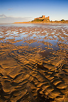 The patterns left by the tide entice you towards the impressive structure of Bamburgh Castle.