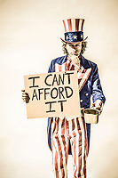 "An unle Sam character with a sign saying ""I can't afford it"" as if he is panhandling."