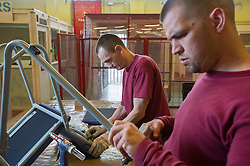 A prisoner welding in a prison workshop making prison chairs