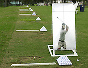 Jason Cohen, a golfer on the NGA Hooters Tour, is reflected in a mirror on the driving range as he practices for the tour event at the Canebrake Country Club in Athens, Ala., Monday, August 30, 2004.  Cohen, from Port Charlotte, FL recently missed two tour events to help his parents recover from hurricane damage.  (AP Photo/The Decatur Daily, Gary Cosby Jr.)