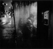 Homeless man lights a cigarette at an outdoor izakaya pub on a rainy winter night in Sanya, Tokyo, Japan.
