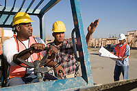 Construction worker showing direction to another worker steering vehicle