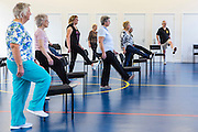 Local elderly members of the community take part in an exercise class using a chair at the Percy centre, Bath Somerset.