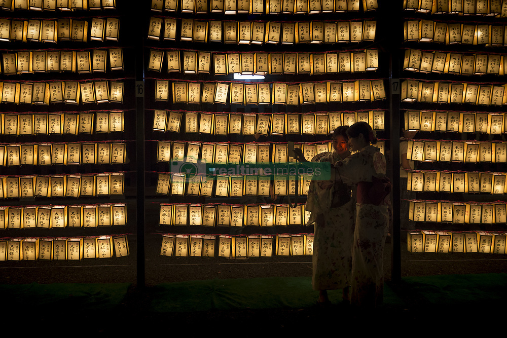 July 13, 2017 - Hiratsuka, Kanagawa, Japan - A visitors takes pictures of a row of paper lanterns with the names of the shrine deveotees, during the festival of ''Mitama'' or departed souls, at Yasukuni shrine in Tokyo, the shrine decorated with about 30,000 lanterns during the three-day summer festival aiming at comforting souls of dead, especially for the war dead. The festival is after Japan's Buddhist custom to honor and comfort souls of family's ancestors. (Credit Image: © Alessandro Di Ciommo via ZUMA Wire)