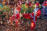 Warming up in the dead leaves - 2000 Santas of all ages take part in the annual Santa Run in Battersea Park to support Noah's Ark Children's Hospice.