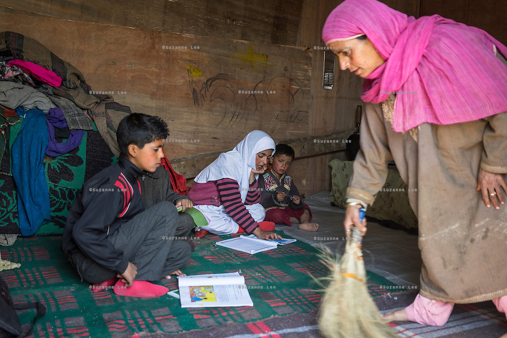 (Alison Griffin to fill in names) (mother's name) cleans the temporary shelter as her children study on the floor of the shelter built next to their collapsed home in Abikarpora village on the Dal Lake, Srinagar, Jammu and Kashmir, India, on 25th March 2015. Since the flood, she has been widowed, and is left with four young children and no home. Her family now lives in a temporary shelter built using the emergency shelter kit, and continues their recovery with the help of relief kits such as education kit, food basket, hygiene kit and non-food items from Save the Children. Photo by Suzanne Lee for Save the Children