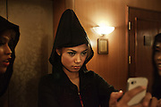 "YANGON,MYANMAR,MARCH 2012: Ha Moon takes a self portrait with her mobile before going on stage at the Traders Hotel,central Yangon.<br /> Burma is a country in Transition. And if that hasn't been made clear enough by the political debates and the recent by-elections, meet the Me N Ma Girls, the first girlband in the country.<br /> The timing couldn't be better. After the April 1st elections in 2012 an always increasing number of investors from all over the world has been visiting Myanmar. After decades of military regime and isolation, the strings of censorship have started loosening up. The government censors in fact for years have banned songs and articles, deleting anything that was seen as ""to provocative"" such as leather outfits and colored wigs.<br /> Describing themselves as Myanmar's first all-girl group, under the management of the Australian dancer and choreographer Nicole May, these five women - coming from either Buddhist or Catholic background and formerly known as Tiger Girls - not only have been challenging censorship laws but they're as well trying to win hearts in a society that in many ways remains man-dominated and socially conservative.<br /> In a country that has been locked up for years, the Me N Ma Girls, embracing western pop culture with skimpy outfits and catchy songs, show with every performance the will of the Burmese youth to come out of a decades-long isolation.<br /> Five girls leading a new form of rebellion: the kind that questions roles and cultural norms."