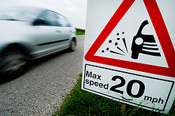 Max speed 20mph sign and loose chippings on a country B road, Leicestershire, England, UK.