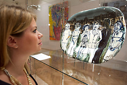 © Licensed to London News Pictures. 08/10/2012. LONDON, UK. A member of Bonhams staff looks at an untitled piece of earthenware, created in 1990 by artist Grayson Perry estimated to fetch GB£8,000-12,000, ahead of an sale at the auction house's New Bond Street premises. The auction, featuring a collection of contemporary art and design is set to take place on Thursday the 11th of October at Bonham's New Bond Street auction house. Photo credit: Matt Cetti-Roberts/LNP
