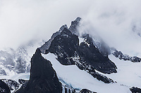 Glaciated mountains covered in rhine ice and shrouded in mist mark the entrance to Drygalski Fiord on the SouthEast coast of South Georgia.  South Sandwich Islands,  Southern Atlantic Ocean.