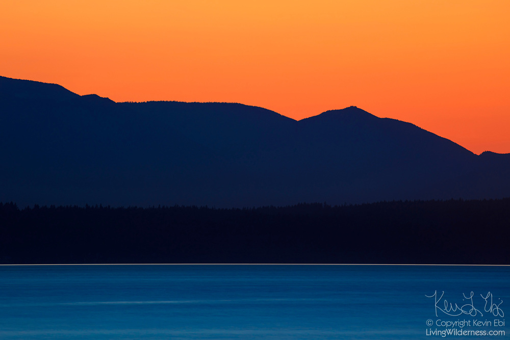 Several peaks in the northern portion of the Olympic Mountain Range stand stall over the blue water of Puget Sound, part of the Salish Sea, at dusk in this view from Golden Gardens Park in Seattle, Washington.