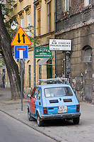 Old car and buildings with signs in Polish on Mostowa Street in Kazimierz Krakow Poland