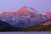 First light of dawn softly illuminates Mount Gould in the Many Glacier region of Glacier National Park, Montana, USA
