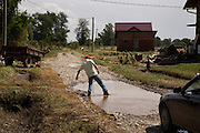A man checks the depth of water on a road in the flood-damaged neighborhood of Naselje Dobor in Modrica, Bosnia and Herzegovina.<br /> <br /> Photo by Matt Lutton / Boreal Collective<br /> <br /> Flooding in Bosnia and Herzegovina.