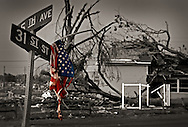 A shredded flag hangs on a street sign in Tuscaloosa following the F-4 tornado that ripped through the town on April 27, 2011, killing 44 people. (Photo by Carmen K. Sisson/Cloudybright)