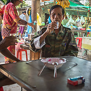 A man sips on rice wine after breakfast in Poom Prey, Cambodia.