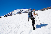A 40's Caucasian woman hikes up the Muir snow field on Mt. Rainier.