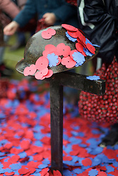 11 November 2018. Lochnagar Crater, La Boisselle, Somme, France. <br /> <br /> The helmet of a fallen soldier is covered in petals. Gathered in the pouring rain, those who perished in the Great War are remembered by British and French civilians on the 100th anniversary of the Great War. <br /> <br /> Lochnagar Crater was created by the Tunnelling Companies of the Royal Engineers under a German field fortification. The explosion was the loudest man made noise created at that time, purportedly heard in London. <br /> <br /> Photo©; Charlie Varley/varleypix.com