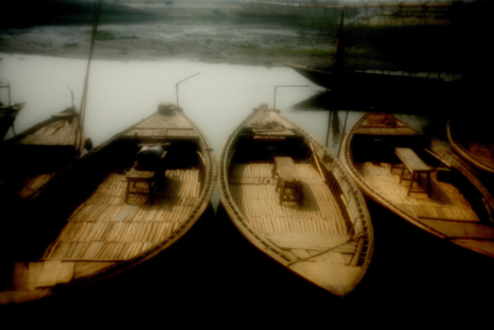 Dream of Dhaka..Boats at the riverbank at the edge of the city...Dhaka, the fastest growing megacity in the world, is flooded by between 4 to 500.000 new people every year. A growth double its entire population of the 1947 census when India was partitioned. The people currently residing in Dhaka is sharing each square kilometer with an average of approximately 20.000 other people. According to local estimates more than 15.000.000 people inhabits the giant metropolis, dubbed by the World Bank as the fastest growing megacity in the world. The exponential growth is progressing towards an expected 25 million people by 2025. The Dreamers of Dhaka more often than not end up as squatters large slums under conditions less than favorable with the unfortunate third; the city-dwellers destitute of rights and land. Solitude, silence and personal space are luxury commodities for the few who can afford to reflect and act upon it in this ever growing society...Photo by: Eivind H. Natvig/MOMENT