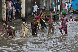 August 3, 2017 - Dhaka, Bangladesh - DHAKA, BANGLADESH - AUGUST 03 : Children playing in water logged by heavy rainfall in Dhaka, Bangladesh on August 03, 2017...Venturing outdoors may become deadly across wide swaths of Bangladesh, India and Pakistan by the end of the century as climate change drives heat and humidity to new extremes, according to a new study...Climate change could soon make it fatal to even go outside in some parts of the world, according to a new study...Temperatures could soar so much in southern Asia by the end of the century that the amount of heat and humidity will be impossible to cope with and anyone going outside would die...The study used new research that looked at the way humidity changes how people's bodies can deal with heat. Temperatures and the amount of moisture will mean that the body will simply be unable to cool itself and so people will die, the researchers found...The regions likely to be hardest hit include northern India, Bangladesh and southern Pakistan, home to 1.5 billion people. (Credit Image: © Zakir Hossain Chowdhury via ZUMA Wire)