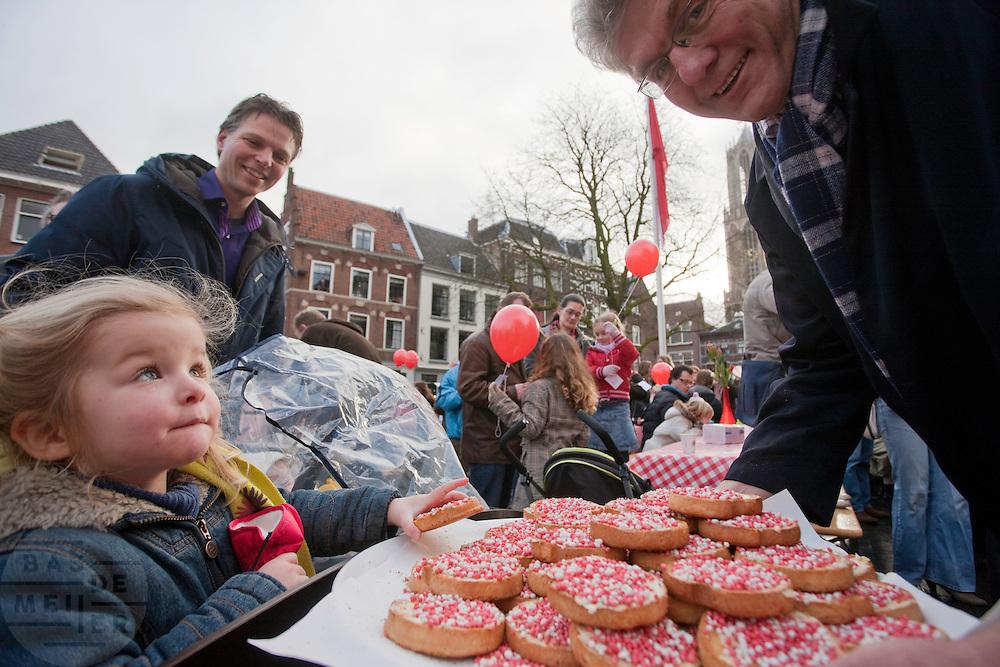 Een meisje pakt een beschuit met rood en witte muisjes van een schaal die een wethouder van Utrecht draagt. De gemeente viert de 300.000 inwoner, Helena Dijkhuizen.
