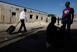 Somali migrant Abririsak Mohamud Anama (L) walks away from his cabin before leaving for France at the Hal Far Reception Centre outside Valletta July 9, 2009. A total of 92 migrants enjoying international protection that prevents their deportation left Malta on Thursday to begin a new life in France as part of an initiative between the French and Maltese authorities, the International Organisation for Migration said. ..