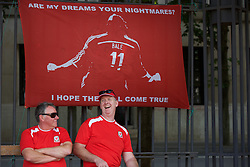 """LYON, FRANCE - Wednesday, July 6, 2016: Two Wales supporters sit in front of a Gareth Bale banner """" Are my dreams your nightmares? I hope there all come true"""" in Lyon ahead of their team's UEFA Euro 2016 Championship Semi-Final match against Portugal. (Pic by Paul Greenwood/Propaganda)"""