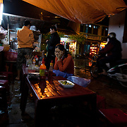 Waiting for a bowl of cao lau noodles under a tarp, in the rain, in an alley in Hoi An, Vietnam.