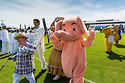"""28 AUGUST 2014 - BANGKOK, THAILAND:     A little person leads a person in an elephant suit during the parade opening the King's Cup Elephant Polo Tournament at VR Sports Club in Samut Prakan on the outskirts of Bangkok, Thailand. The tournament's primary sponsor in Anantara Resorts. This is the 13th year for the King's Cup Elephant Polo Tournament. The sport of elephant polo started in Nepal in 1982. Proceeds from the King's Cup tournament goes to help rehabilitate elephants rescued from abuse. Each team has three players and three elephants. Matches take place on a pitch (field) 80 meters by 48 meters using standard polo balls. The game is divided into two 7 minute """"chukkas"""" or halves.   PHOTO BY JACK KURTZ"""