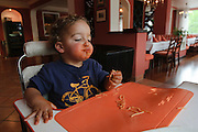 Young boy of two eats spaghetti with his hands