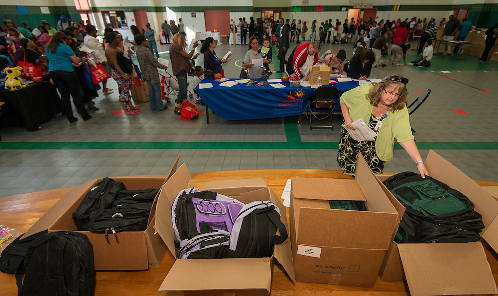 A volunteer distributes backpacks with school supplies during the Hilliard Fall Festival, October 24, 2013. Free shoes were distributed to all the students and parents were able to sign up for services and receive books and backpacks for their children.