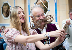 A woman takes a selfie with a competitor of the fourth British Beard and Moustache Championships at the Empress Ballroom, Winter Gardens, Blackpool.