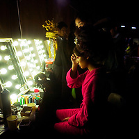 BEIJING, MAY -7, 2012 : a model adjusts her make-up  before Guo Pei's fashion show. ..Guo Pei , 45, is China's answer to haute couture. When she started out 15 years ago, there was no fashion in China .  Since then though  about everything in China has changed. Many more people are able to afford luxury products, and Chinese women, at least those who can afford it, follow international fashion trends. What makes Guo Pei different is what she puts on a runway. She employs 300 people in a workroom two hours from Beijing. She had to train them, but it?s also true that her creative freedom is tethered to relatively cheap labor. One dress alone, made entirely of golden panels, took 50,000 hours to embroider.