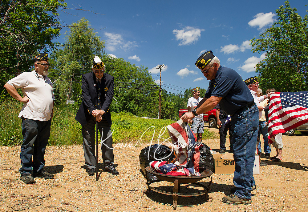From VFW Post 58 Steve Bracy and Bill Firth Commander District 7 look on as Vice Commander David Schroth adds an american flag to the fire during the Flag Retirement ceremony at the Belmont covered Bridge Saturday afternoon.   (Karen Bobotas/for the Laconia Daily Sun)