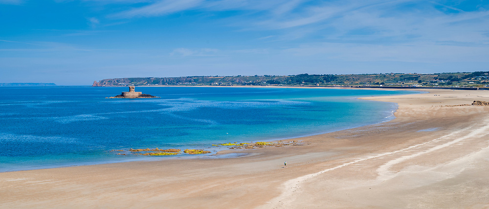 Rocco Tower deep blue sea and lone tourist on sandy St Ouen's Beach in St Brelade region, west coast of Jersey, Channel Isles