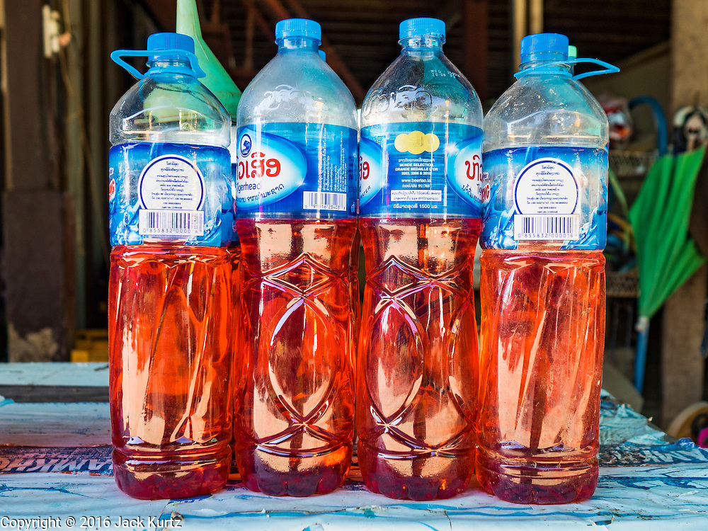 19 JUNE 2016 - DON KHONE, CHAMPASAK, LAOS: Gasoline for sale in recycled water bottles on Don Khone. Don Khone Island, one of the larger islands in the 4,000 Islands chain on the Mekong River in southern Laos. The island has become a backpacker hot spot, there are lots of guest houses and small restaurants on the north end of the island.    PHOTO BY JACK KURTZ