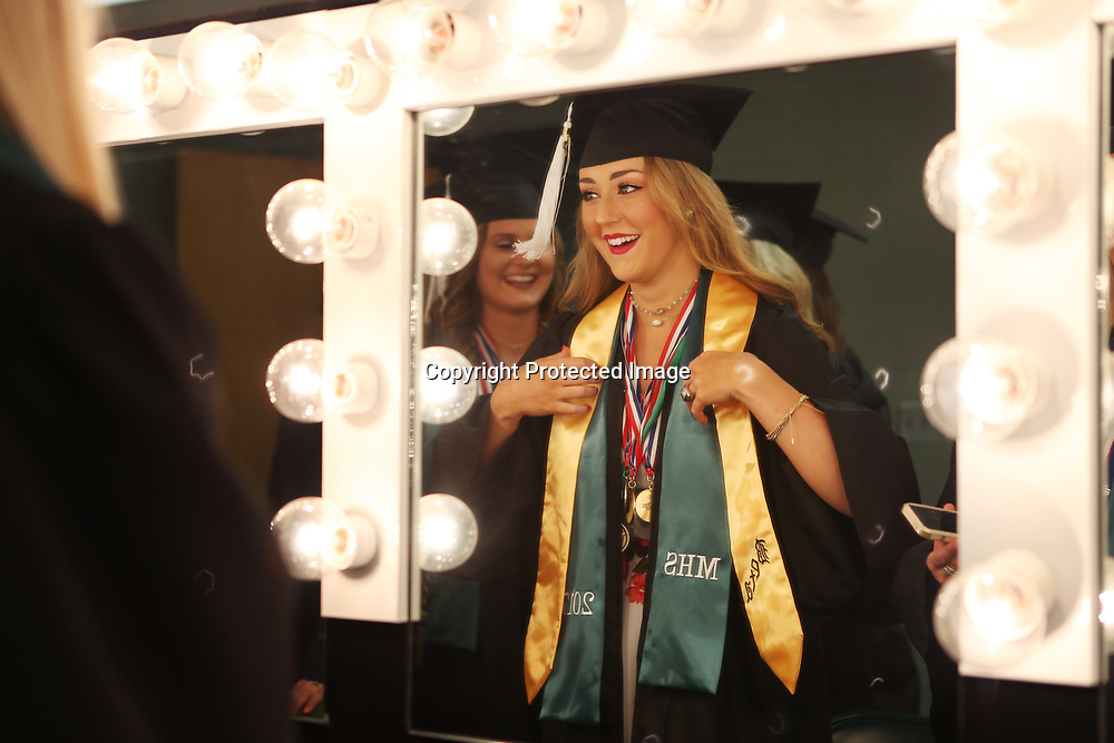 Mooreville High School senior Madison Walton puts on her Beta stole in the mirror before the start of Mooreville's graduation ceremony Saturday afternoon at the BancorpSouth Arena.