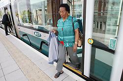 Woman stepping off a tram onto the platform,