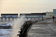 © Licensed to London News Pictures. 30/11/2013. Southwold, UK A man walks along the saffron toward Southwold Pier. Crashing waves on the seafront in Southwold, Suffolk today, 30 November 2013. Photo credit : Stephen Simpson/LNP