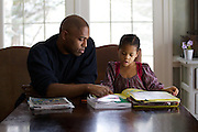 Shaun Alexander helps his daughter Eden, 6 yrs old, with school work at their home in Great Falls, VA, January 21, 2014.