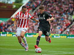 STOKE-ON-TRENT, ENGLAND - Sunday, August 9, 2015: Liverpool's Adam Lallana in action against Stoke City's Geoff Cameron during the Premier League match at the Britannia Stadium. (Pic by David Rawcliffe/Propaganda)