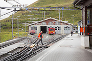 Workman crossing the tracks at the train station in Kleine Scheidegg, Switzerland