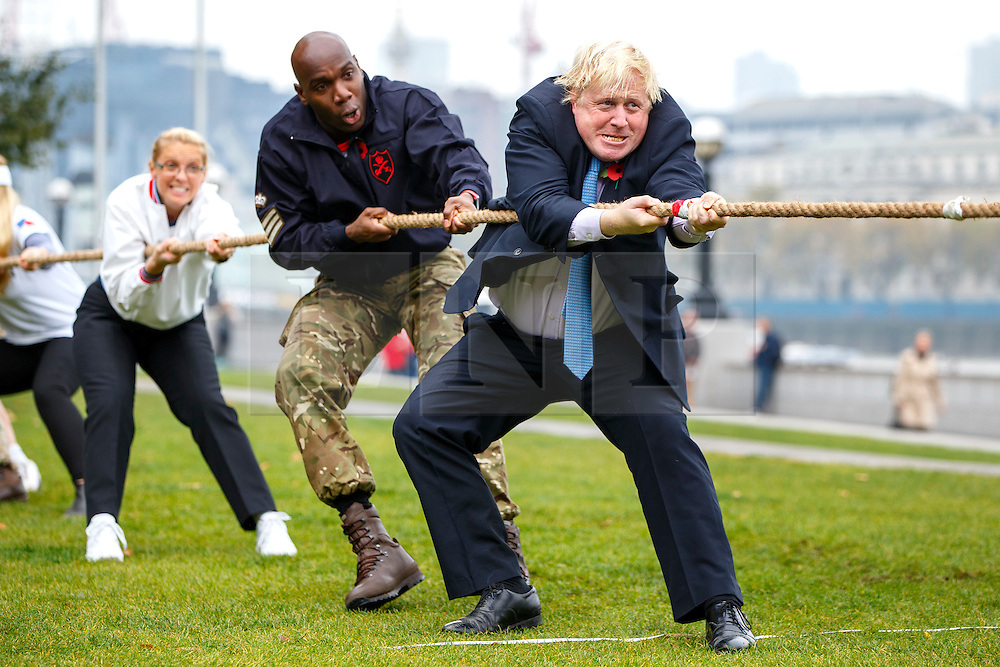 © Licensed to London News Pictures. 27/10/2015. London, UK. Mayor of London Boris Johnson joins Armed Forces personnel for a Tug of War to launch London Poppy Day in Potters Fields in London on Tuesday, 27 October 2015. Photo credit: Tolga Akmen/LNP