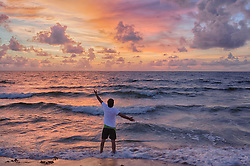 man standing in the Atlantic Ocean welcoming the sunrise in Fort Lauderdale, Florida