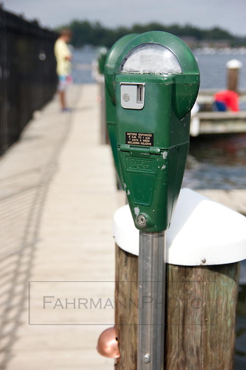 Two boaters dock at a boat slip with parking meters in Excelsior, Minnesota on Lake Minnetonka.