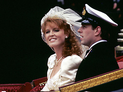 The Duke and Duchess of York (formerly Prince Andrew and Miss Sarah Ferguson) smile happily during their carriage procession after their wedding at Westminster Abbey in London.