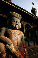Guardian at Bhaktapur Durbar Square with its large brick-paved area in the centre, surrounded by temples arranged in a harmonious layout named by UNESCO as a World Heritage Site.